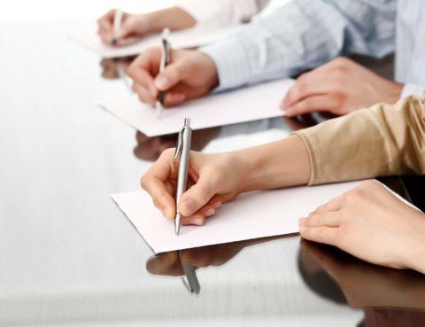 Row of writing human hands